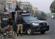 Police officers stand guard at a deserted road due to strikes called by the the country's religious political parties over the security forces's crackdown against a banned Tehreek-e-Labaik Pakistan party, in Karachi, Pakistan, Monday, April 19, 2021. An outlawed Pakistani Islamist political group freed 11 policemen almost a day after taking them hostage in the eastern city of Lahore amid violent clashes with security forces, the country's interior minister said Monday. (AP Photo/Fareed Khan)