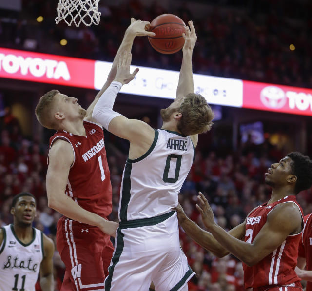 Wisconsin's Brevin Pritzl (1) blocks a shot by Michigan States's Kyle Ahrens (0) during the first half of an NCAA college basketball game Tuesday, Feb. 12, 2019, in Madison, Wis. (AP Photo/Andy Manis)