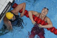 Margaret MacNeil, right, of Canada, reacts after winning the final of the women's 100-meter butterfly as Sarah Sjoestroem, of Sweden, looks on at the 2020 Summer Olympics, Monday, July 26, 2021, in Tokyo, Japan. (AP Photo/David J. Phillip)