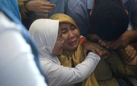Relatives of passengers comfort each other as they wait for news on a Lion Air plane that crashed off Java Island - Credit: AP