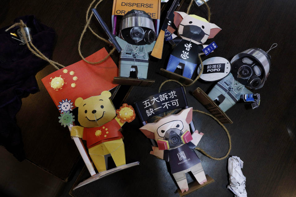 Paper figures of police officers, protesters and Winnie the Pooh, with messages in support of the pro-democracy movement are removed at a restaurant in Hong Kong, Thursday, July 2, 2020. Hong Kong police have made the first arrests under a new national security law imposed by mainland China, as thousands of people defied tear gas and pepper pellets to protest against it. Police say they arrested 10 people under the law, including at least one who was carrying a Hong Kong independence flag. (AP Photo/Kin Cheung)