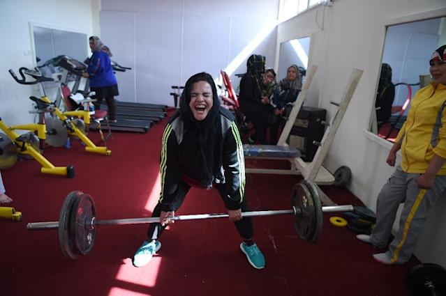 Parhiz strains during a deadlift exercise as teammate Sadya Ayubi looks on at a training session (AFP Photo/WAKIL KOHSAR)