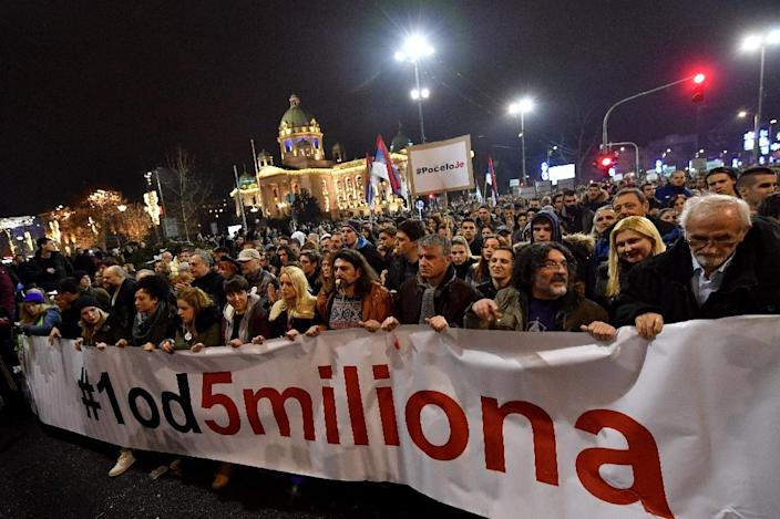 """Thousands of people, many blowing whistles, hold a banner that reads, """"One out of five million"""", as they protested against the Serbian president in Belgrade last month (AFP Photo/ANDREJ ISAKOVIC)"""