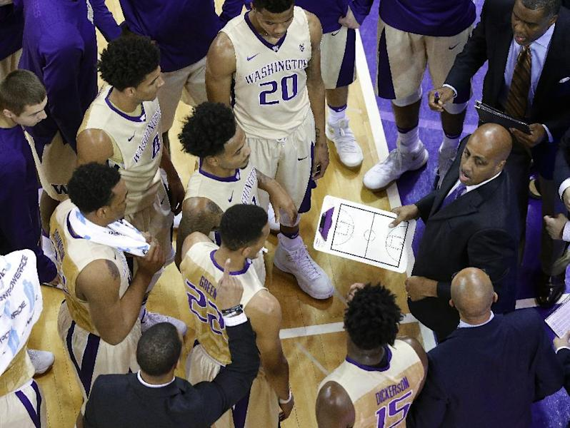 FILE - In this Dec. 20, 2016, file photo, Washington coach Lorenzo Romar, holding clipboard at right, talks to his team during a timeout in the team's NCAA college basketball game against Cal Poly in Seattle. Washington announced Wednesday, March 15, 2017, that Romar had been fired after 15 seasons at the school. (AP Photo/Ted S. Warren, file)