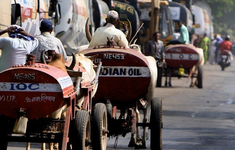 Indian men drive bullock carts used for transporting oil in Mumbai on April 23, 2008