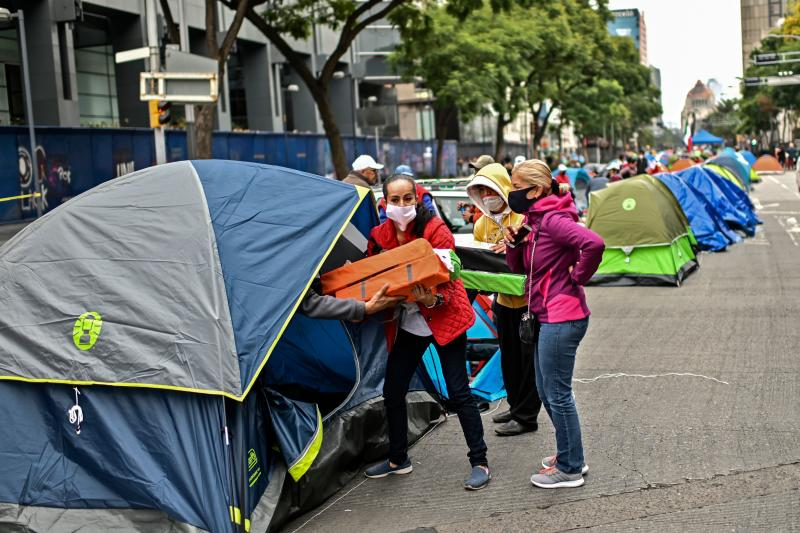 Members of the National Front Anti-AMLO (Frena), who will make a second attempt to reach Zocalo Square to protest against Mexican President Andres Manuel Lopez Obrador (ALMO), distribute tents as they camp on Juarez street in Mexico City on September 20, 2020, a day after being prevented by the local police to get to the city's main square, amid the COVID-19 novel coronavirus pandemic. (Photo by PEDRO PARDO / AFP) (Photo by PEDRO PARDO/AFP via Getty Images)