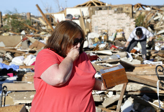 Kelli Kannady weeps after finding a box of photographs of her late husband in the rubble near what was her home in Moore, Oklahoma May 21, 2013. Rescuers went building to building in search of victims and thousands of survivors were homeless on Tuesday after a massive tornado tore through the Oklahoma City suburb of Moore, wiping out whole blocks of homes and killing at least 24 people. Kannady's husband was not killed during the tornado. REUTERS/Rick Wilking (UNITED STATES - Tags: DISASTER ENVIRONMENT) - RTXZVQ6