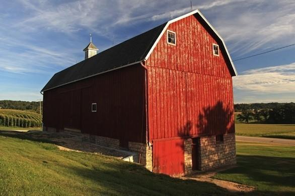 The Weber barn, north of St. Donatus, is a large red barn with a single cupola, two small upper windows and a limestone foundation.