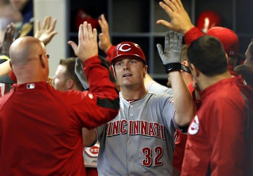 Reds Jay Bruce gets high fives in the dugout after hitting a three-run homer off of Brewers Marco Estrada during the fourth inning of a baseball game Monday, May 7, 2012, in Milwaukee. (AP PhotoTom Lynn)