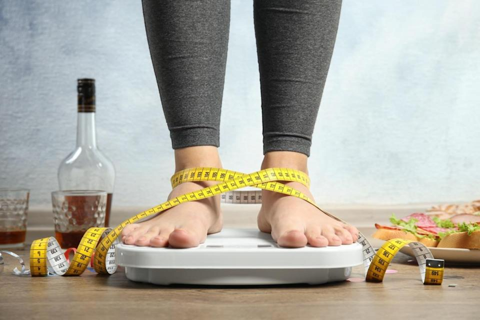 Woman with measuring tape using scale surrounded by food and alcohol after party on floor