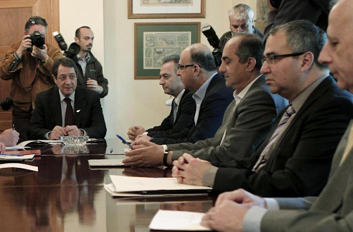 During a crucial top level meeting of Cypriot leaders including from left to right, Cyprus President Nicos Anastasiades, ruling DISY party deputy leader Averof Neophytou, DIKO party boss Marios Garoyian, EVROKO party leader Demetris Syllouris, Cyprus Central Bank Governor Panicos Demetriades, and Central Bank Deputy Governor Spyros Stavrinakis, during a crucial meeting to find an alternative plan to raise 5.8 billion euros to finance a bailout at the Presidential palace in Nicosia Wednesday, March 20, 2013. Cypriot lawmakers have rejected a critical draft bill that would have seized part of people's bank deposits in order to qualify for a vital international bailout. (AP Photo/Petros Giannakouris)