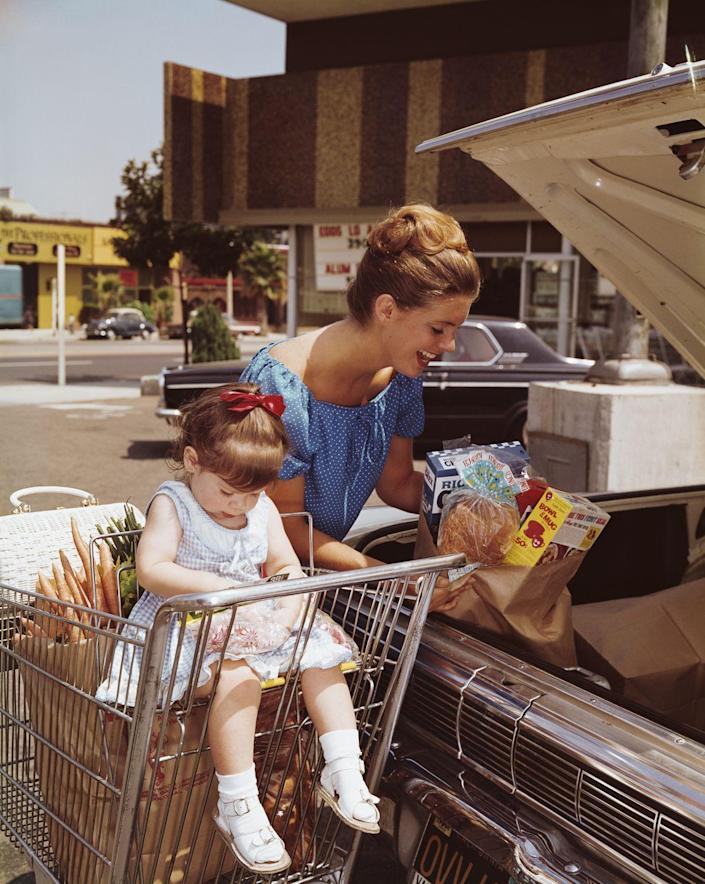 <p>A mother loads groceries into the trunk of her car while her daughter helps herself to a bag of candy.</p>
