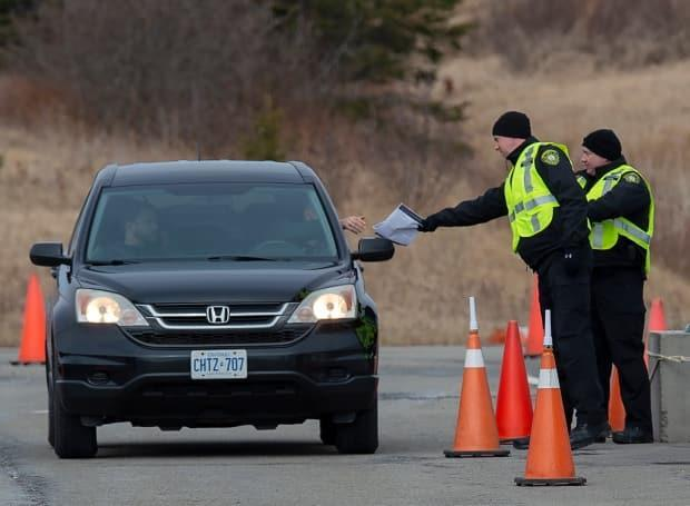 Compliance officers check vehicles at the Nova Scotia-New Brunswick border near Amherst in April 2020. Many Nova Scotians are asking the Liberal government for a clearer re-opening plan. (Andrew Vaughan/The Canadian Press - image credit)