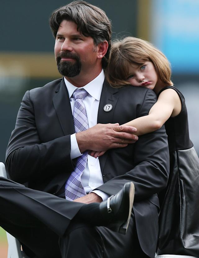 With his daughter Gentry Grace, right, at his side, retired Colorado Rockies first baseman Todd Helton listens to speakers during a ceremony to retire his number before the Rockies host the Cincinnati Reds in a baseball game in Denver on Sunday, Aug. 17, 2014. (AP Photo/David Zalubowski)