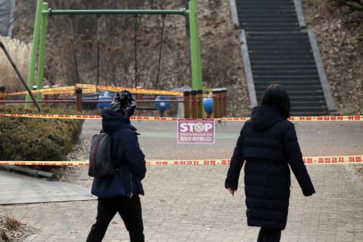 Visitors look at a playground, which is taped off for the social distancing measures and a precaution against the coronavirus at a park in Seoul, South Korea, Wednesday, Dec. 23, 2020. South Korea has added more than 1,000 new coronavirus cases in a resurgence that is erasing hard-won epidemiological gains and eroding public confidence in the government's ability to handle the outbreak. (AP Photo/Lee Jin-man)