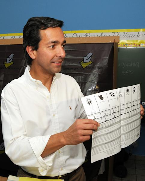 "In this image released by the New Progressive Party, Puerto Rico's Gov. Luis Fortuno shows his ballot to the press as he votes at a polling station in Guaynabo, Puerto Rico, Tuesday, Nov. 6, 2012. Puerto Ricans are electing a governor as the U.S. island territory does not get a vote in the U.S. presidential election. But they are also casting ballots in a referendum that asks voters if they want to change the relationship to the United States. A second question gives voters three alternatives: become the 51st U.S. state, independence, or ""sovereign free association,"" a designation that would give more autonomy. (AP Photo/New Progressive Party, Jerry Guillen)"