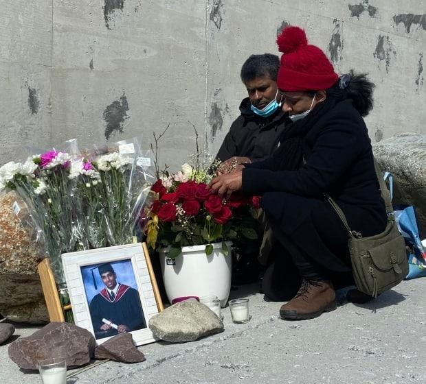 Don and Chadima Jayasinghe arrange flowers at a memorial for their son Supul in Flatrock on Saturday.  The 21-year-old was last seen in the area after he slipped and fell into the ocean. (Heather Gillis/CBC - image credit)