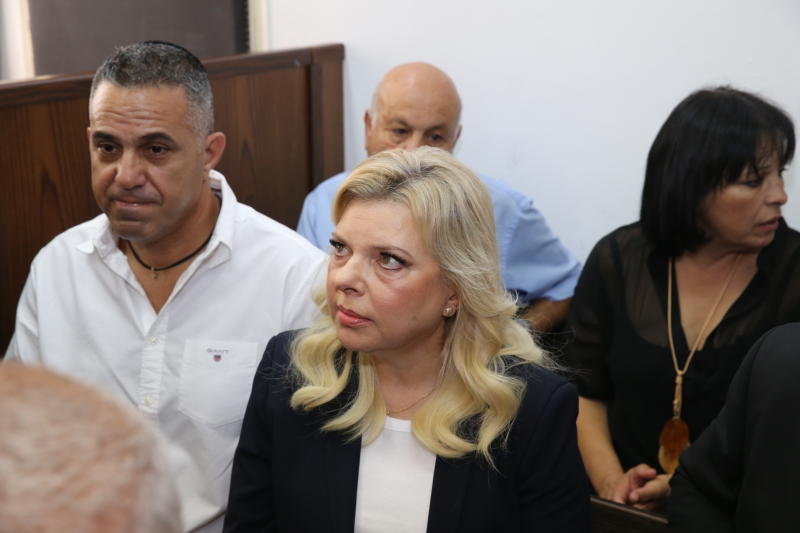 File - In this Sunday, Oct. 7, 2018 file photo, wife of the Israeli Prime Minister Benjamin Netanyahu, Sara, center, sits in a courtroom in Jerusalem. Prosecutors say that Mrs. Netanyahu has agreed to a plea bargain settling allegations that she misused some $100,000 of state money on lavish meals. The State Attorney's office said Mrs. Netanyahu will pay roughly $15,000 in fines to close the case, which accused her of running up large tabs at luxury restaurants while hiding that the official residence employed a full-time chef. (Amit Shabi, Yedioth Ahronoth, Pool via AP, File)