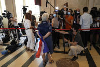 A participant in the attacks trial, holding a French flag, answers reporters as she arrive at the special courtroom Wednesday, Sept. 8, 2021 in Paris. In a secure complex embedded within a 13th-century courthouse, France on Wednesday will begin the trial of 20 men accused in the Islamic State group's 2015 attacks on Paris that left 130 people dead and hundreds injured. (AP Photo/Michel Euler)
