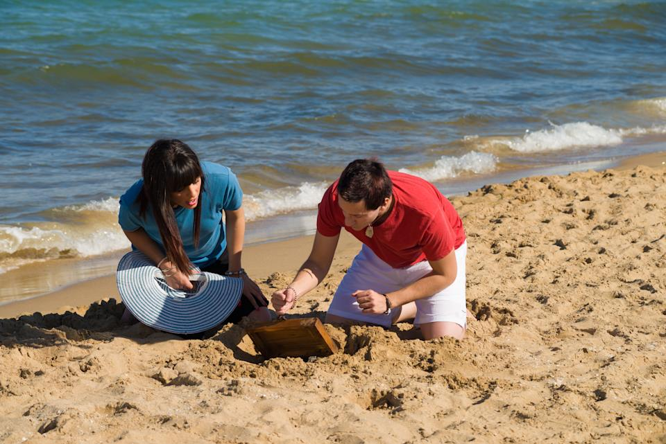Couple discovering a treasure on the beach, a concept
