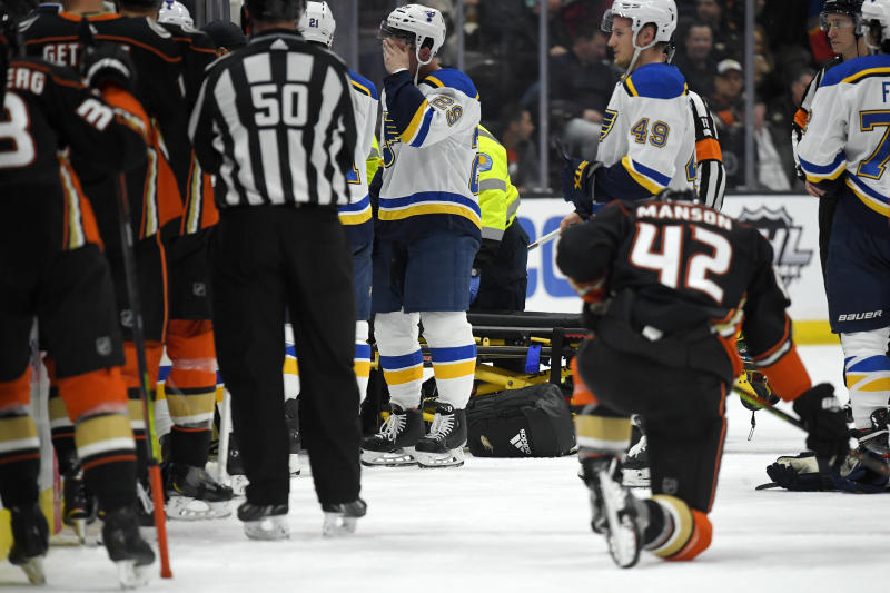 St. Louis Blues defenseman Vince Dunn, left, of center wipes his faces as Anaheim Ducks defenseman Josh Manson kneels on the ice while blues defenseman Jay Bouwmeester, who suffered a medical emergency, is worked on by medical personnel during the first period of an NHL hockey game Tuesday, Feb. 11, 2020, in Anaheim, Calif. (AP Photo/Mark J. Terrill)
