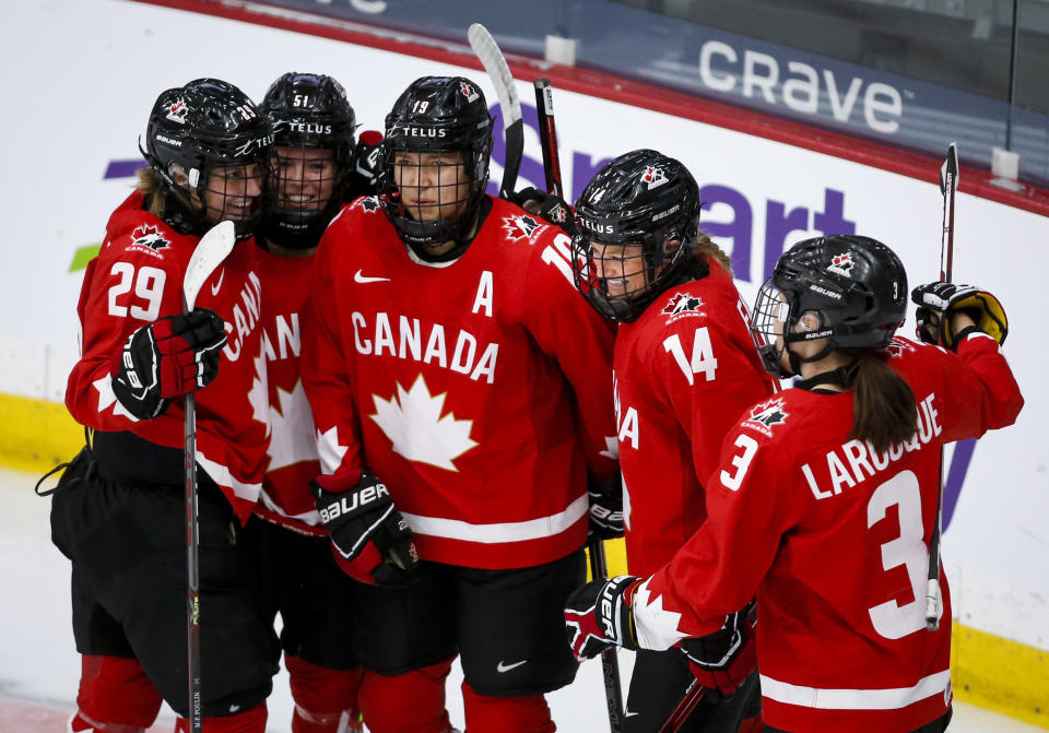 Canada's Renata Fast (14) celebrates her goal against Switzerland with teammates during the first period of an IIHF women's hockey championships semifinal in Calgary, Alberta, Monday, Aug. 30, 2021. (Jeff McIntosh/The Canadian Press via AP)