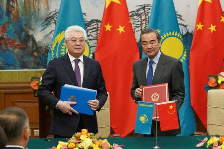 Kazakh Foreign Minister Beibut Atamkulov (L) and Chinese Foreign Minister Wang Yi (R) pose for photos after signing documents at the end of a meeting at Diaoyutai State Guesthouse in Beijing, China March 28, 2019. Andrea Verdelli/Pool via REUTERS