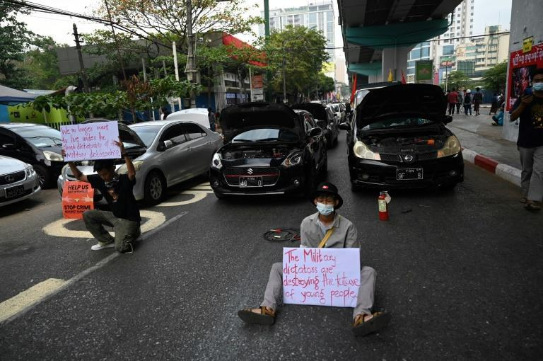 Protesters in Myanmar's biggest city Yangon have blockaded roads with vehicles, leaving their bonnets up and pretending they were broken down