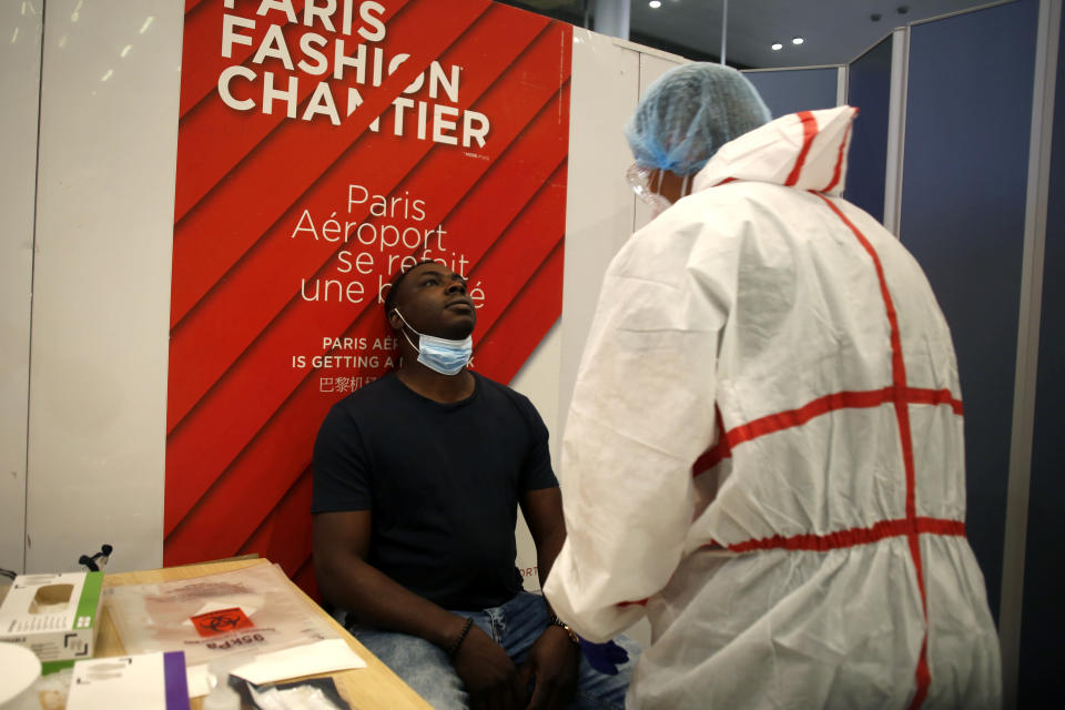 A health worker is going to collect a nasal swab sample for COVID-19 test, at the Roissy Charles de Gaulle airport, outside Paris, Saturday, Aug. 1, 2020. Travelers entering France from 16 countries where the coronavirus is circulating widely are having to undergo virus tests upon arrival at French airports and ports.(AP Photo/Thibault Camus)