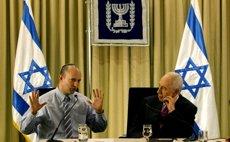FILE - In this Thursday, Jan. 31, 2013 file photo, Israel's President Shimon Peres, right, sits with Naftali Bennett, head of Israel's Jewish Home party, during their meeting at the President's residence in Jerusalem. Israeli Prime Minister Benjamin Netanyahu reached an agreement Thursday to form a new coalition government that is expected to try to curb years of preferential treatment for the country's ultra-Orthodox minority and may push for restarting peace efforts with Palestinians. (AP Photo/Sebastian Scheiner)