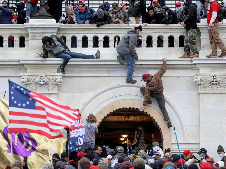 <p>A mob of supporters of former US President Donald Trump fight with members of law enforcement at a door they broke open as they storm the US Capitol Building in Washington, DC, on 6 January 2021</p> ((Reuters))