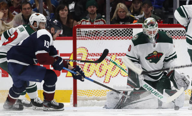 Minnesota Wild goaltender Devan Dubnyk, right, stops a redirected shot off the stick of Colorado Avalanche right wing Valeri Nichushkin, front left, who drives past Wild center Luke Kunin to the net in the second period of an NHL hockey game Friday, Dec. 27, 2019, in Denver. (AP Photo/David Zalubowski)
