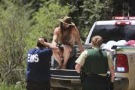 Physician John Hartberg, left, speaks to county and federal officials about an elderly patient being rushed out of a remote encampment on Friday, July 2, 2021, in the Carson National Forest, outside of Taos, N.M.. Hartberg, from New Orleans, was attending the annual Rainbow Gathering where the man fell ill. The condition of the man was not immediately known. (AP Photo/Cedar Attanasio)