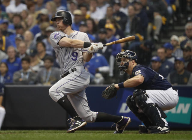 Colorado Rockies' DJ LeMahieu hits a single during the third inning of Game 2 of the National League Divisional Series baseball game against the Milwaukee Brewers Friday, Oct. 5, 2018, in Milwaukee. (AP Photo/Jeff Roberson)