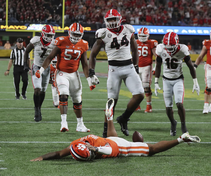 Clemson quarterback D.J. Uiagalelei is knocked to the turf by Georgia defender Travon Walker on a broken play during the second half of an NCAA college football game Saturday, Sept. 4, 2021, in Charlotte, N.C. (Curtis Compton/Atlanta Journal-Constitution via AP)
