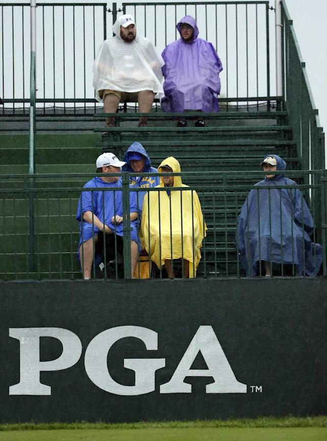 Golf fans sit in the rain on range before the second round of the PGA Championship golf tournament at Valhalla Golf Club on Friday, Aug. 8, 2014, in Louisville, Ky. (AP Photo/David J. Phillip)