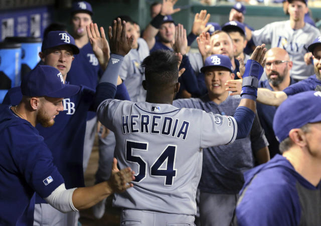 Tampa Bay Rays' Guillermo Heredia (54) is greeted in the dugout after scoring on a single by Joey Wendle during the fifth inning of the team's baseball game against the Texas Rangers on Tuesday, Sept. 10, 2019, in Arlington, Texas. (AP Photo/Richard W. Rodriguez)