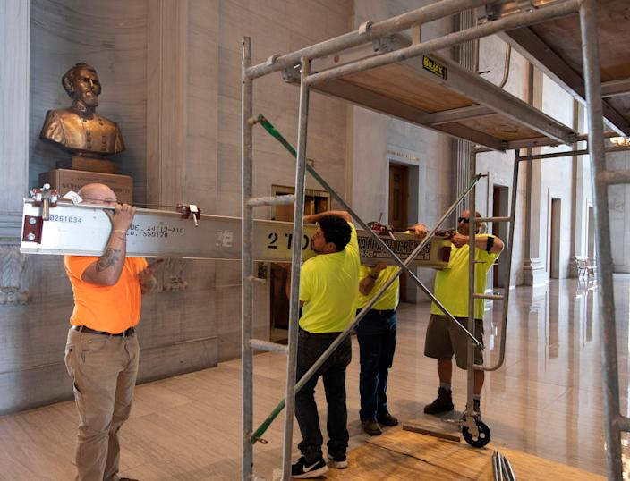 Workers prepare scaffolding in front of a bust of Confederate General and early Ku Klux Klan leader Nathan Bedford Forrest at the State Capitol Thursday, 22 July 2021 in Nashville, Tennessee.  (AP)
