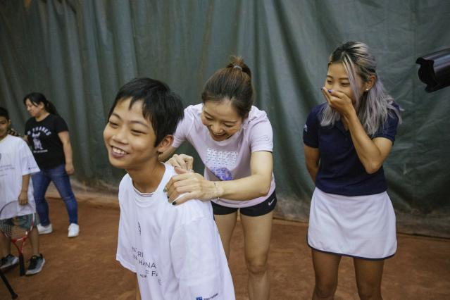 Two-time Grand Slam champion Li Na signs a tee-shirt for one of the students attending the clinic she led at the Sutton East Tennis Club Thursday, July 18, 2019, in New York. Li Na will be inducted into the Tennis Hall of Fame on Saturday, July 20. (AP Photo/Kevin Hagen)