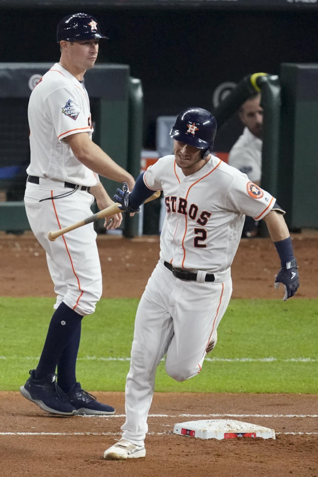 Houston Astros' Alex Bregman hand his bat to first base coach Don Kelly after a home run against the Washington Nationals during the first inning of Game 6 of the baseball World Series Tuesday, Oct. 29, 2019, in Houston. (AP Photo/Eric Gay)