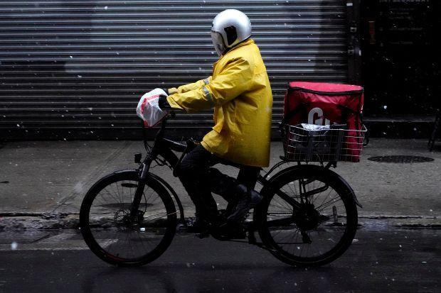A delivery person rides his bike in the snow in the Manhattan borough of New York City