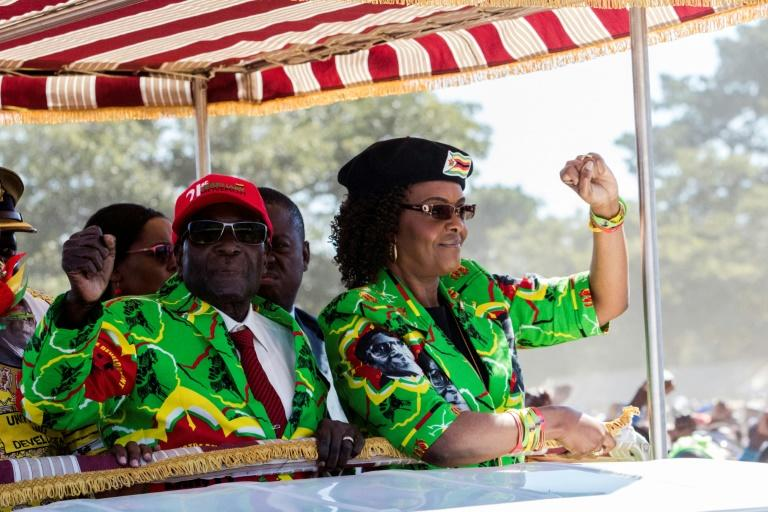 Zimbabwe President Robert Mugabe (L) with his wife Grace raise their fists before meeting delegates during a Zimbabwe ruling party ZANU-PF youth rally at Rudhaka Stadium in Marondera on June 2, 2017