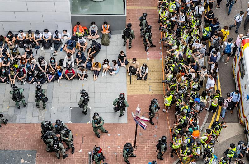 Police circle detainees near the city's legislature on May 27, as the debate over the national-security bill was set to resume   Miguel Candela—EPA-EFE/Shutterstock