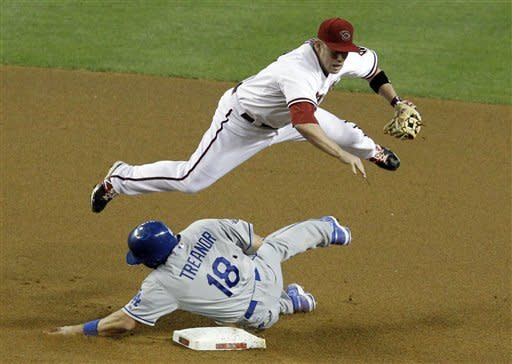 Arizona Diamondbacks' Aaron Hill leaps over Los Angeles Dodgers' Matt Treanor (18) after forcing him out at second base during the fourth inning of a baseball game, Monday, May 21, 2012, in Phoenix. (AP Photo/Ross D. Franklin)