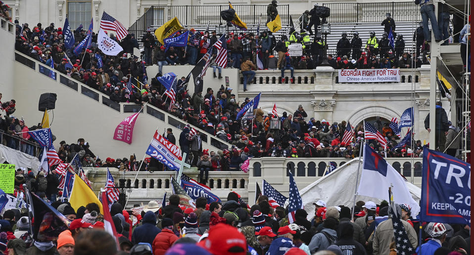 A crowd storms the US Capitol building.