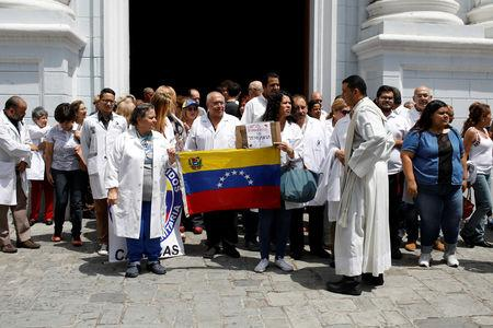 """Venezuelans, including doctors, gather outside a church after a mass during an ongoing blackout in downtown Caracas, Venezuela March 10, 2019. Banner reads """"Humanitarian crisis in Venezuela"""". REUTERS/Marco Bello"""