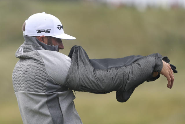 Dustin Johnson of the United States takes off rain coat as he practices on the driving range ahead of the start of the British Open golf championships at Royal Portrush in Northern Ireland, Wednesday, July 17, 2019. The British Open starts Thursday. (AP Photo/Jon Super)