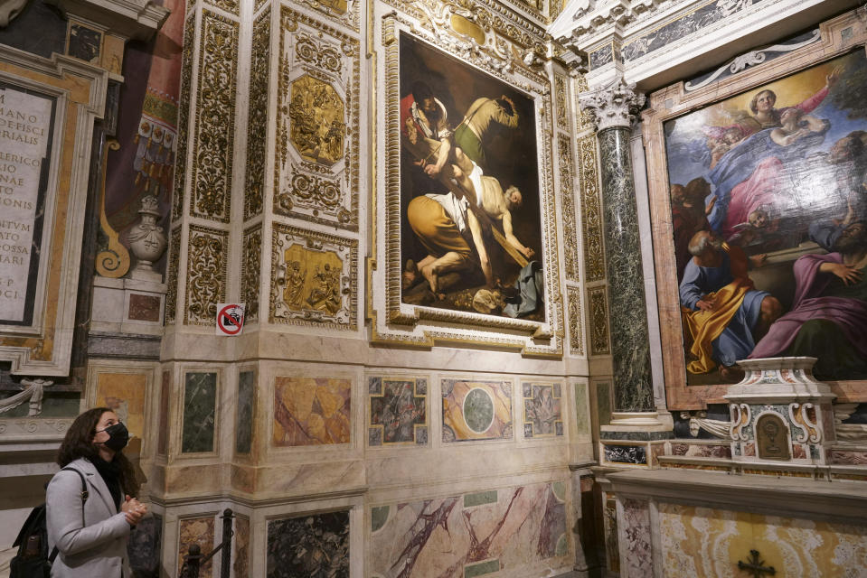 "A woman wearing a face mask to curb the spread of COVID-19 admires paintings he Cerasi Chapel of Santa Maria del Popolo church, Rome, Friday, Dec. 11, 2020. At left is ""The Crucifixion of St. Peter"", 1601, by Renaissance master Michelangelo Merisi, known as Caravaggio, and at right, ""The Assumption of the Virgin"", 1601, by Annibale Carracci. Like elsewhere in Europe, museums and art galleries in Italy were closed this fall to contain the spread of COVID-19, meaning art lovers must rely on virtual tours to catch a glimpse of the treasures held by famous institutions such as the Uffizi in Florence and the Vatican Museums in Rome. However, some exquisite gems of Italy's cultural heritage remain on display in real life inside the country's churches, some of which have collections of renaissance art and iconography that would be the envy of any museum. (AP Photo/Andrew Medichini)"