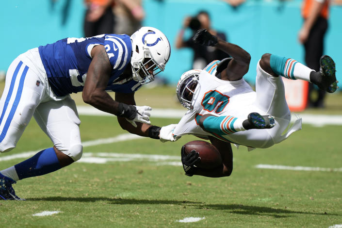 Indianapolis Colts defensive end Tyquan Lewis (94) brings down Miami Dolphins wide receiver Jakeem Grant (19), during the second half of an NFL football game, Sunday, Oct. 3, 2021, in Miami Gardens, Fla. (AP Photo/WIlfredo Lee)