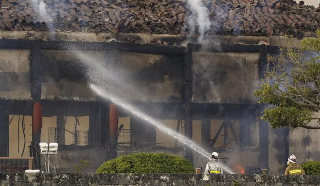 Firefighters battle remnants of the blaze. Photo: Kyodo